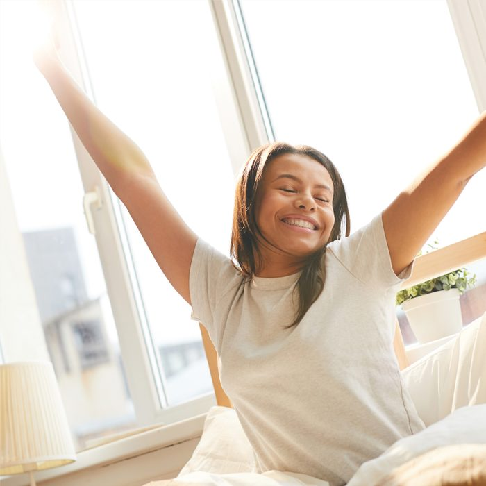 Mixed-Race woman stretching sitting in bed lit by sunlight girl black morning sleep healthy