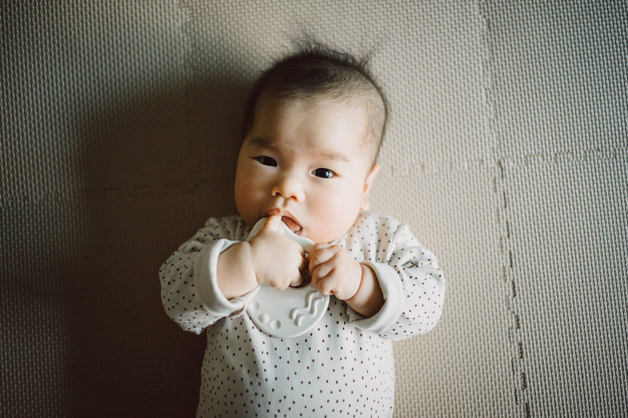 baby girl teething on toy