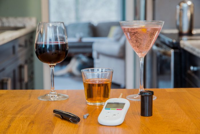 diabetes tools and alcoholic drinks on kitchen table