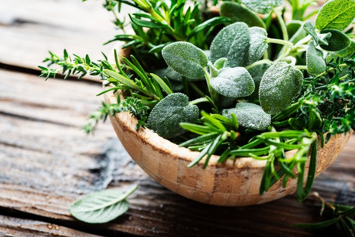 sage leaves in bowl with other herbs