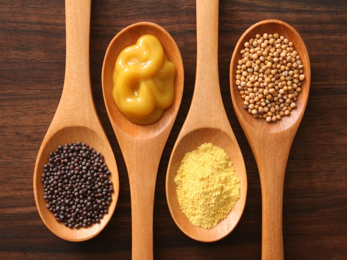 four spoons with varieties of mustard shot from above