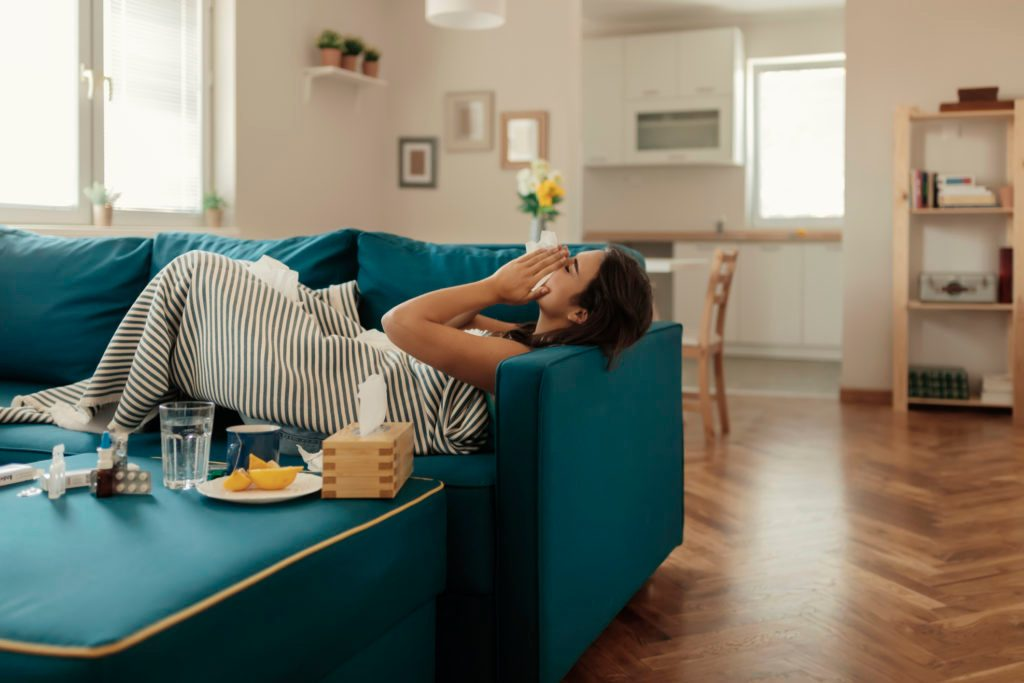 woman laying on couch at home sick with cold or flu