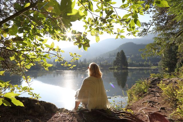 personal mantra woman sitting near lake looking off into distance