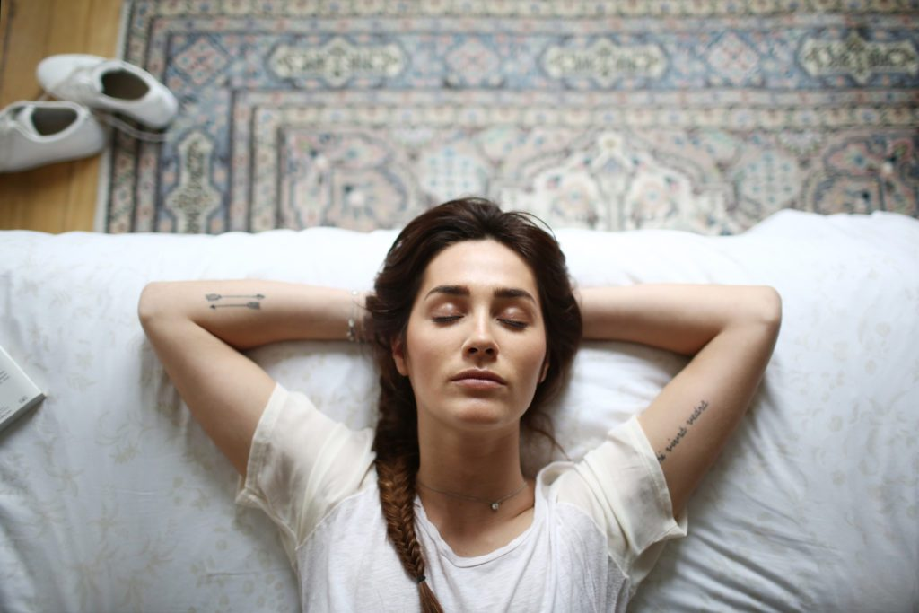 woman calming her thoughts laying on bed