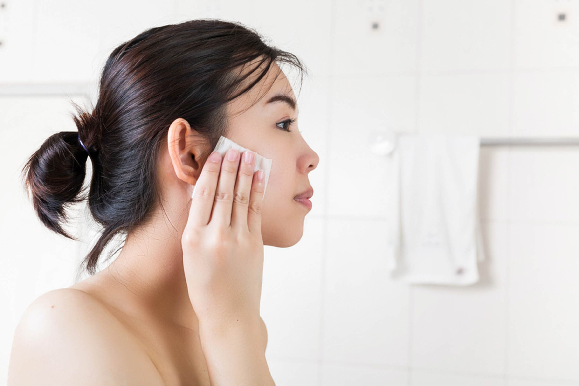 young woman washing face with toner