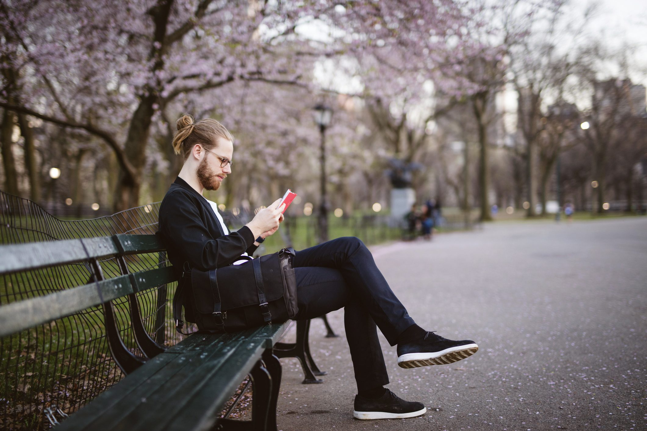 man sitting on park bench reading a book
