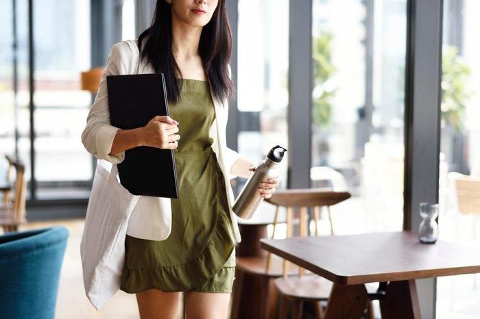 woman walking out of a meeting with water bottle and notebook