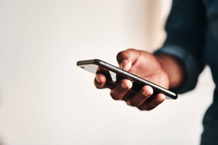 close up of man holding smartphone