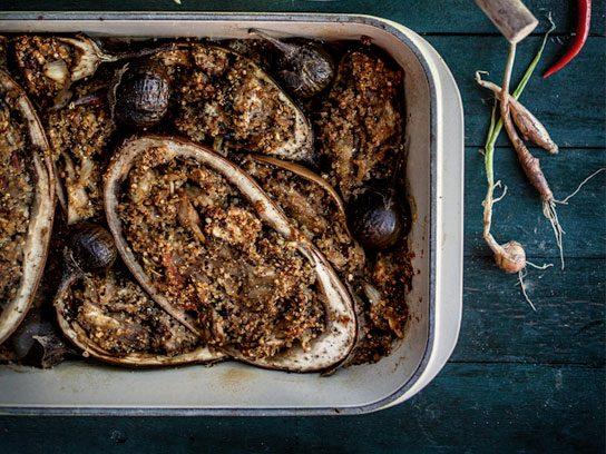 Quinoa-stuffed eggplant in a casserole dish.