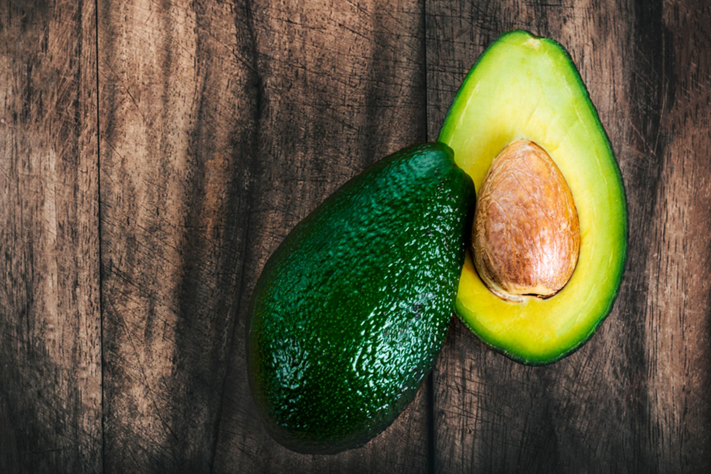 Halved avocado on a wood background