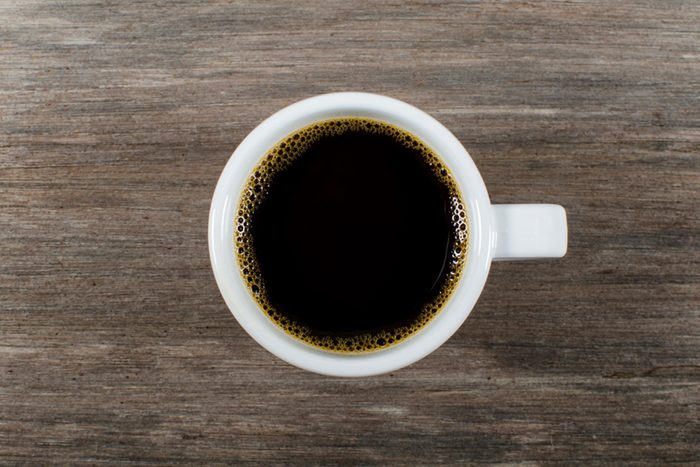 Mug of coffee on wooden background