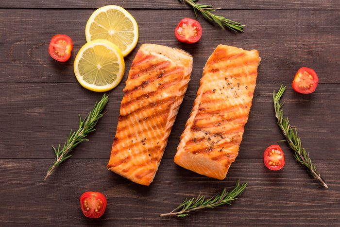 Two grilled salmon filets with rosemary, tomatoes, and lemon slices
