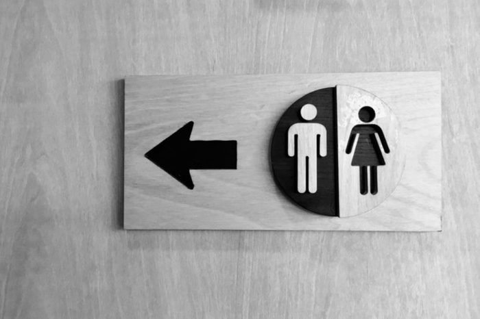 bathroom sign with arrow and male/female symbols