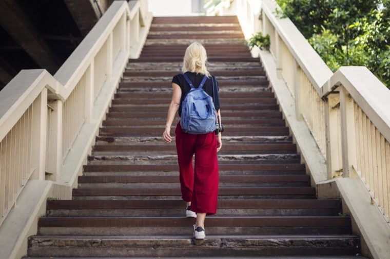 woman with backpack walking up outdoor stairs