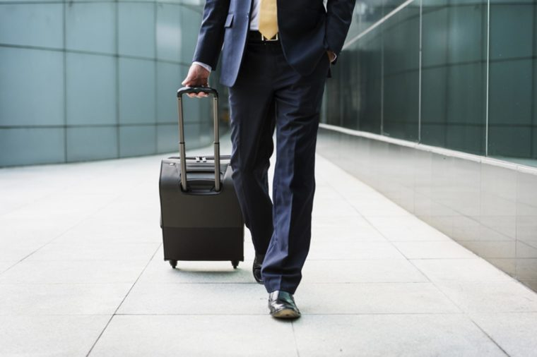 man in business suit walking with roller suitcase