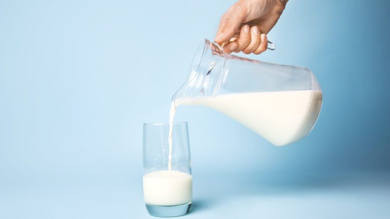 pouring glass of milk blue background