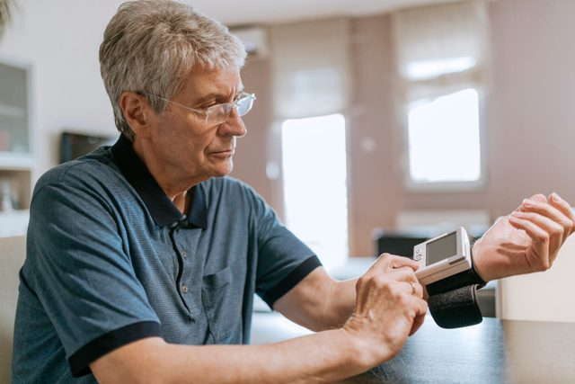 senior man checking his blood pressure at home