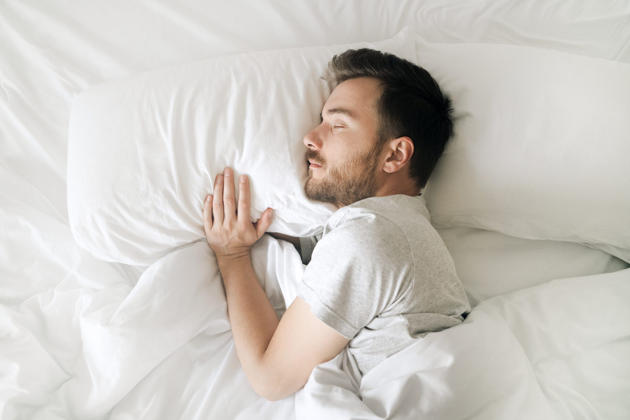man sleeping in bed, holding his pillow
