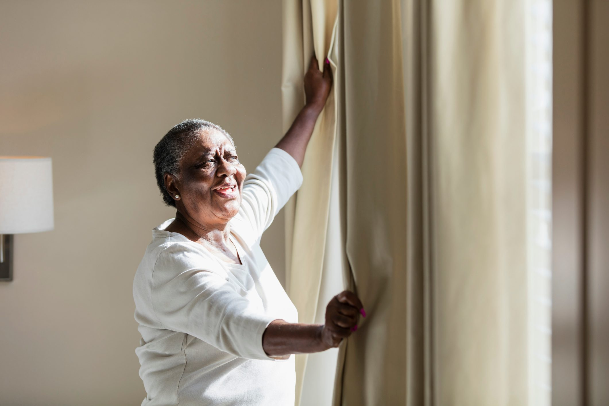 senior woman opening window curtains at home