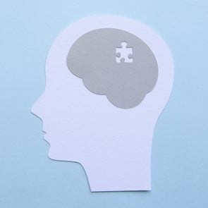 memory concept; paper cutout of human head with puzzle piece missing in the brain