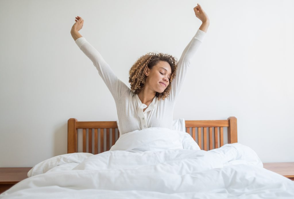 woman waking up in the morning yawning and stretching