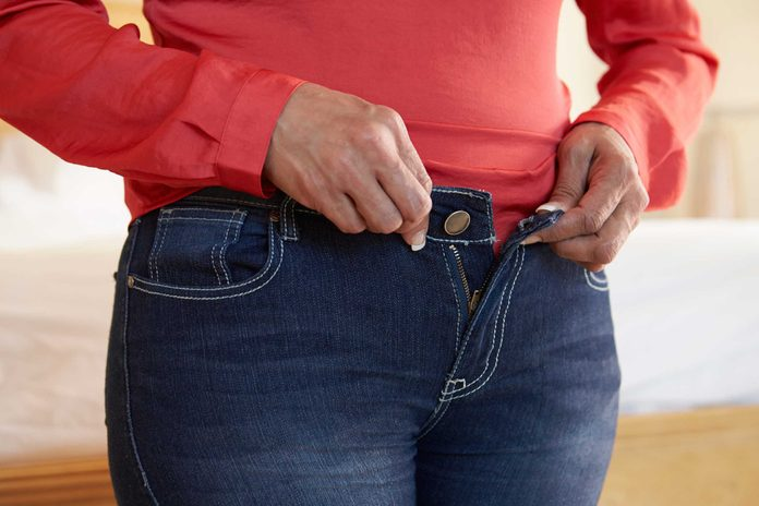 person trying to button tight pants