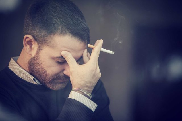 unhappy white man with beard smoking with head in hand