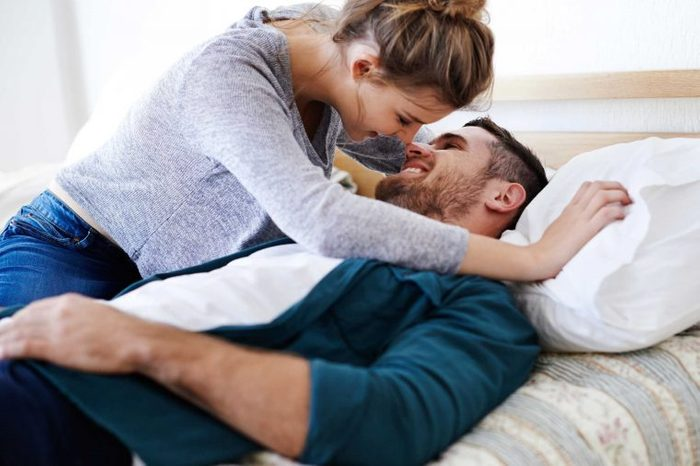 Woman kissing man in bed