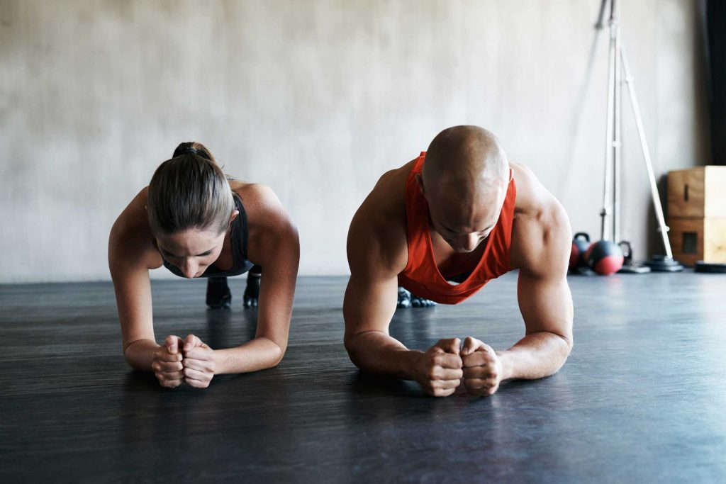 fit man and woman doing plank together