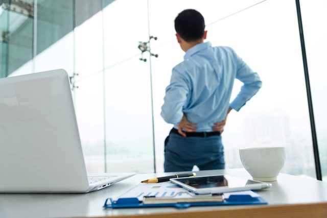 man in office hands on hips and stretching