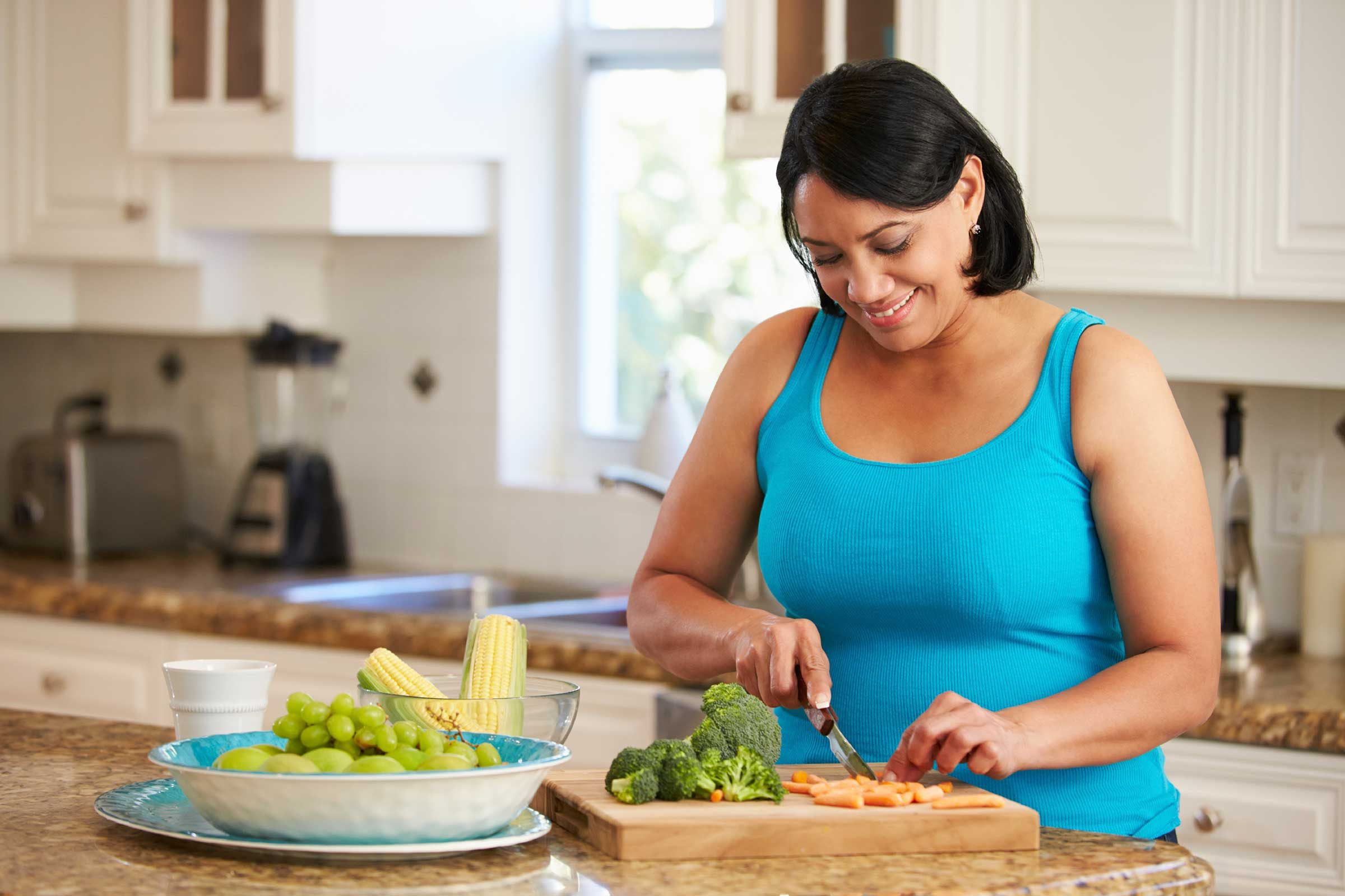 woman cutting up vegetables in the kitchen