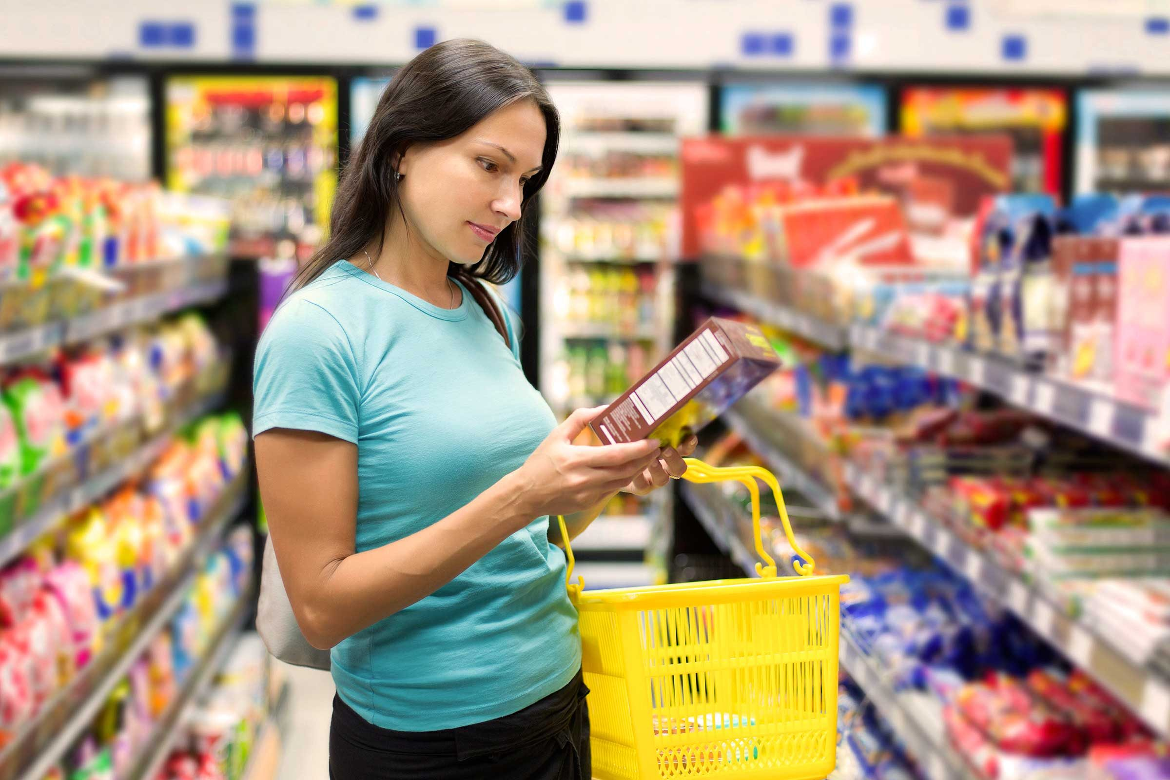 woman shopping, looking at nutrition label