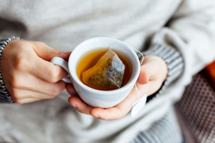 Person in a gray sweater holding a mug of tea.