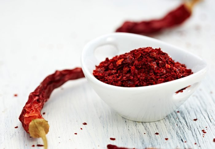 cayenne pepper flakes in a bowl surrounded by whole dried peppers