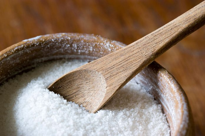 wooden bowl full of salt with wooden spoon