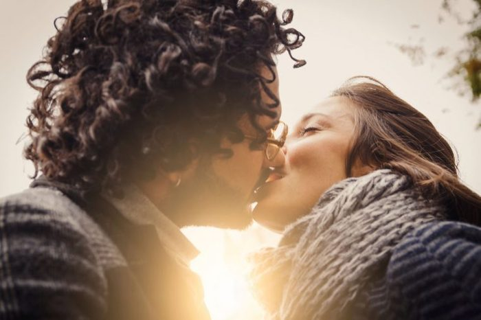 couple kissing with sun in background