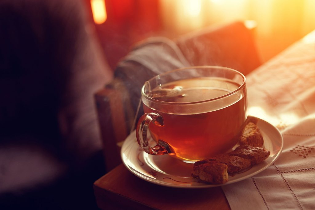 glass mug of tea on saucer