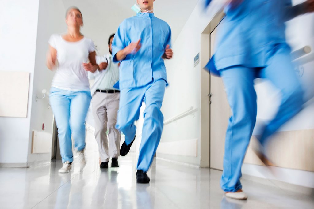 hospital staff running through a hall