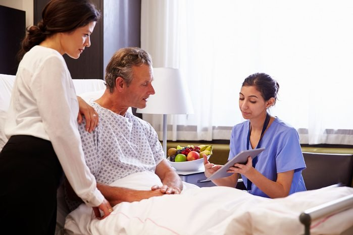 man in hospital bed with family listening to female doctor