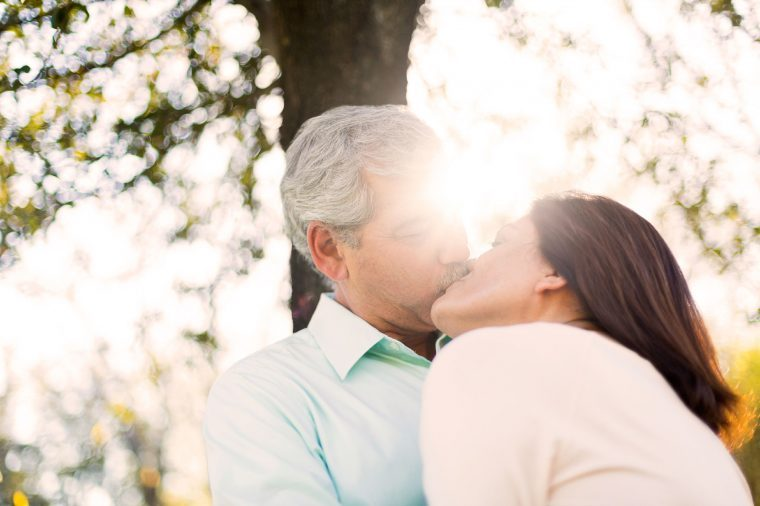 elderly couple kissing outdoors, sun shining through trees in background