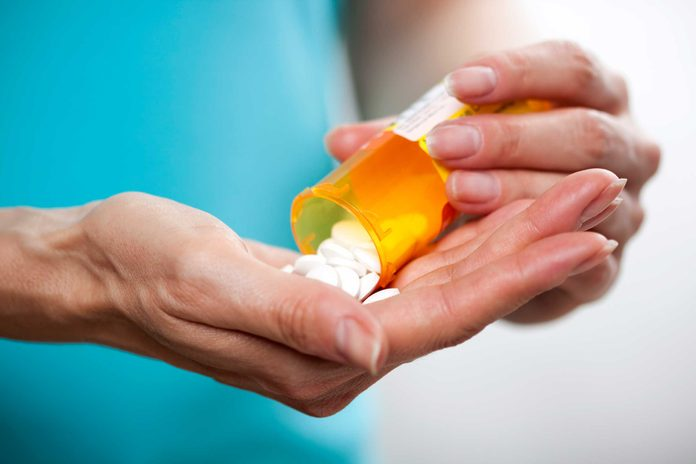 person holding pill bottle and pills