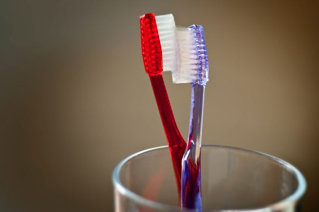 red and purple toothbrushes in a glass