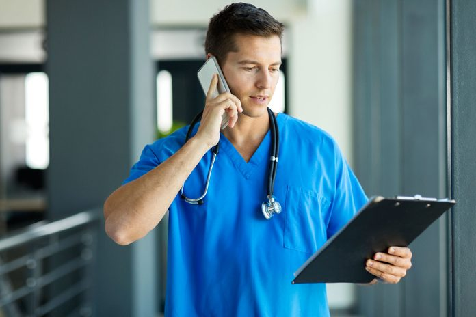 Young doctor on a phone and looking at a clipboard