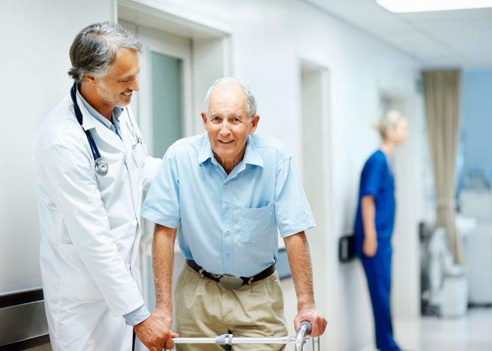 doctor helping an elderly man using a walker in a hospital hall