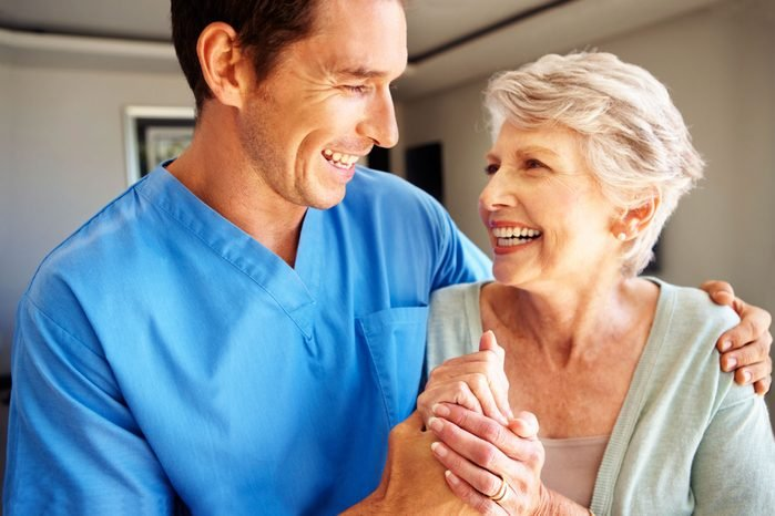 doctor with his arm around an elderly woman