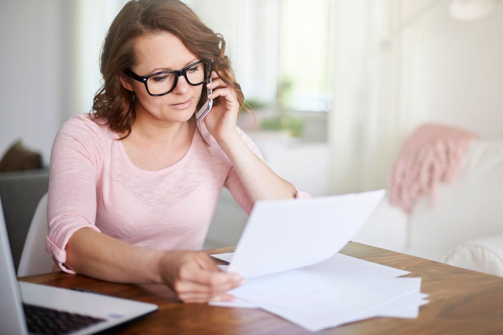 Woman at home analyzing hospital bill over the phone