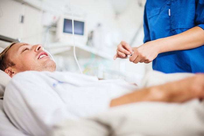 man in a hospital bed being attended to