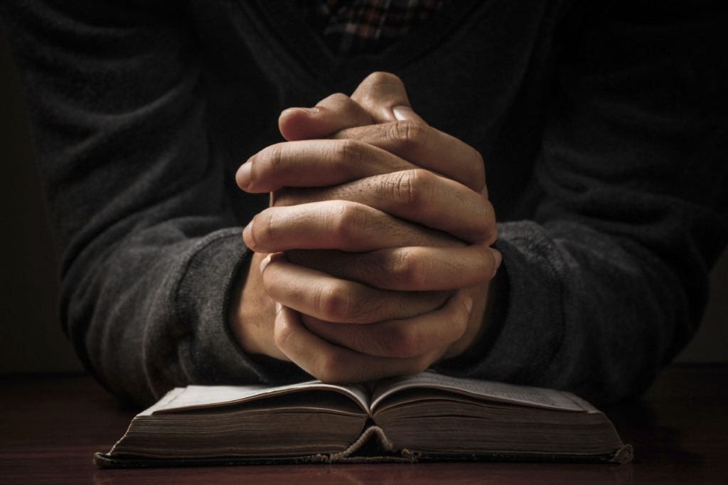 hands folded in prayer over bible