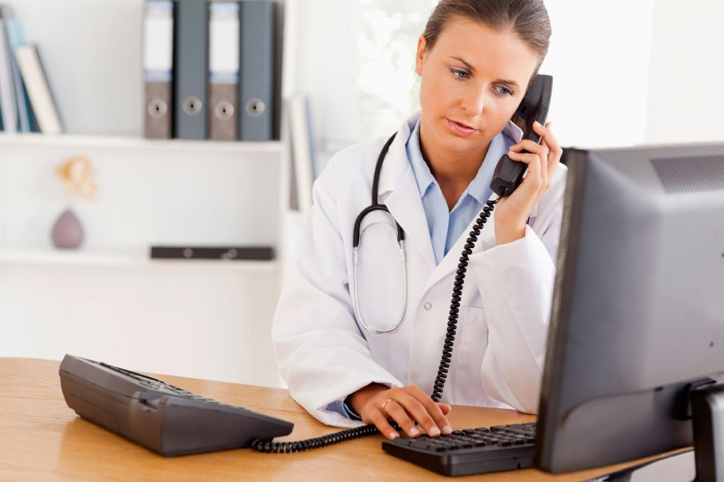 female doctor on phone looking at a computer screen