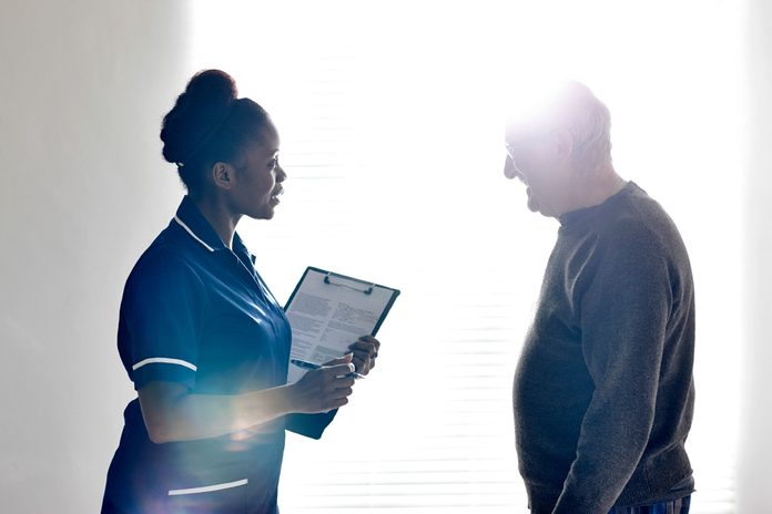 black nurse discussing care with elderly man
